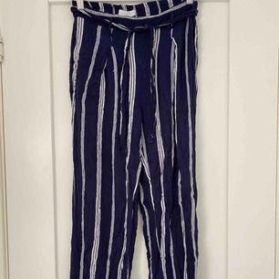 Mörkblå och vita byxor i rak modell, bälte i midjan. Tunt och skönt material!  Köparen står för frakten !