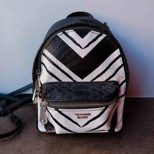 Helt ny mini bagpack från Victoria's Secret!  Tror att det är orm eller krokodilimitation i mönstret.  Små och nätta axelremmar medföljer. Alla dragkedjor fungerar utmärkt. Fina detaljer!  Kan mötas upp eller fraktas (+66kr) posten