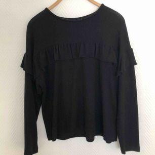 En fin svart mysig tröja med en volang runt hela tröjan  Använd 1 gång frakt ingår ej