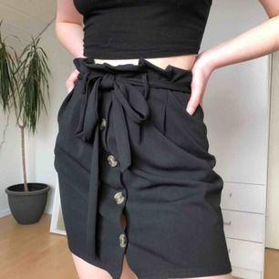 Jättesöt svart kjol med knappar och knytning i midjan!✨ Helt oanvänd 🤩 Frakten kan alltid diskuteras 🖤