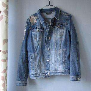 Snygg jeansjacka med blomdetaljer. Den är använd men i väldigt bra skick! Inköpspris - 450 kr Mitt pris - 350 inklusive frakt 💖 Kolla gärna in mina andra plagg som jag säljer 💕