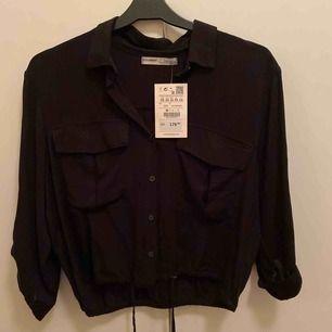 """Säljer denna svarta helt oanvända skjortan (med prislappar kvar) från Pull&Bear. Skjortan har ett band där nere, dom man kan knyta så den blir lite """"fluffig"""" eller strunta i att knyta, lika fint både och:) köparen står för frakten"""