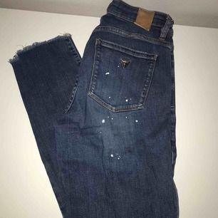 Jeans från Guess som är i nyskick med hål på knäna och vitt färgstänk och andra fina detaljer.