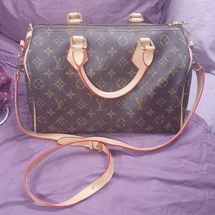 Handväska köpt på marknad, så ej original. Avtagbar rem. Mått: ca. L34 x H22 x B18 cm. Använd men ser bra ut :) Gratis frakt med Postnord (Spårbart). Det går även bra att hämta i GNESTA.