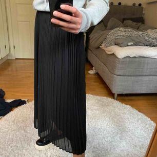 En svart långkjol med stretchigt midjeband. (Frakt ingår inte i priset)