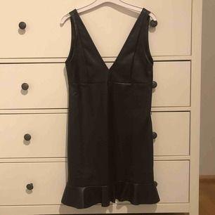 Trendig och snygg mörkbrun (nästan svart) faux-leather klänning med volang nedtill. Jättesnygg att ha en t-shirt under men funkar även utan. Säljer pga brist på användande. Säljaren står för frakt!