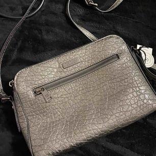 En liten grå silver väska. Jättefin och är helt ny.  Nypris är 500kr. Säljer för endast 200kr. Pga fel färg.  Kan skicka mer bilder vid intresse.