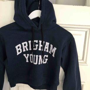 Kort /croppad hoodie från Beyond retro. Köpt för 400kr. Marinblå med vitt tryck. Sitter väldigt snyggt på. Magtröja hoodie.