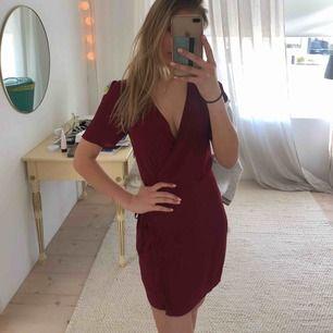 Superfin vinröd klänning med knytning i sidan. Tunt material, perfekt till sommaren.
