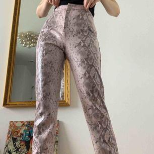 Otroligt coola faux läder byxor i ett rosa ormskinns mönster!⭐️De är endast provade och med lappen kvar som syns i andra bilden. Inköpta för €48 från märket Missguided. Säljer för att de är för stora, tyvärr. Köparen står för frakten!