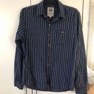 Snygg skjorta i mörk blått med röda och vita detaljer med knappar och en bröstficka. Knappt använd. Passar även L.