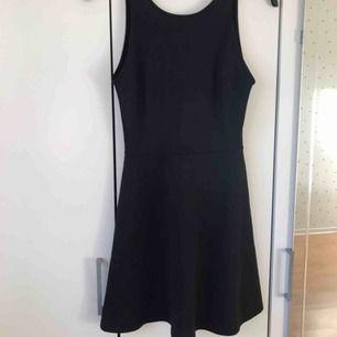Enkel fin svart klänning med lite volanger längst ner och en skarp urringning i ryggen. I fint skick!