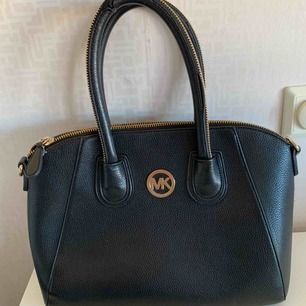 MK, Rymlig väska med rejäl dragkedja och handtag i svart och guld. Mellanstorlek. Fått i present (kan ej garantera äktheten (bra kvalitet) Hittar inte bärremmen, snyggare dock att bara bära den. Liten bit upptill på handtaget defekt (syns knappt)