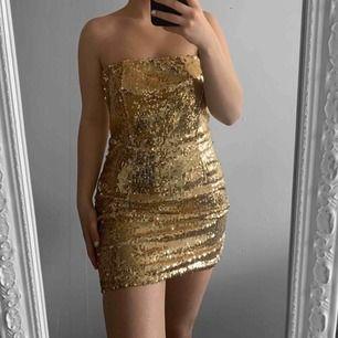 Kort guldfärgad tubklänning från In The Style storlek 8 (36) silikon på insidan så den ej glider ner. Fint skick.  Möts upp i Stockholm eller fraktar. Frakt kostar 59kr extra, postar med videobevis/bildbevis. Jag garanterar en snabb pålitlig affär!✨