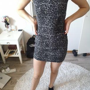 En grå leopardklänning från märket size 8 needle, I nyskick, aldrig använd. Sitter tajt på kroppen. Priset är exklusive frakt