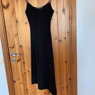 Svart klänning som är snedskuren ner till, en XS men  passar en S , köparen står för frakten.