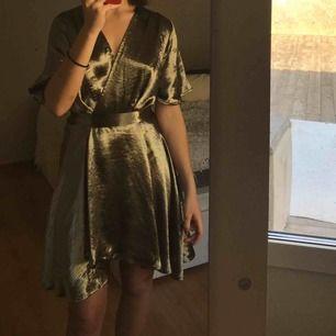 Olive metallic wrap over dress från NA-KD. Klänningen är i superbra skick och är perfekt till sommaren! Priset är inklusive frakt