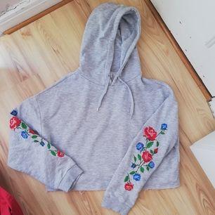 En vacker grå croppad hoodie med broderade blommor på armarna. Nästan inte använd alls. På hoodiens kant så hänger trådar vilket är meningen! Frakt tillkommer och jag tar bara swish 🌼