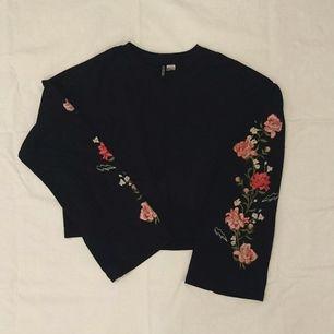 Nice tröja i marinblå med blommor broderade på ärmarna. Storlek S men passar både större och mindre beroende på hur man vill ha den. Hög i midjan. Frakt ingår och pris går alltid att diskutera