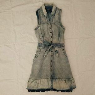 Söt jeansklänning med marinblå spets nedtill. Knappar hela vägen och skärp i midjan. Två fickor vid höften. Frakt ingår i priset 💃 Står 36 på lappen men funkar även för 38