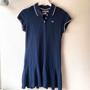 Jättesöt pikéklänning i marinblått med ljusrosa detaljer, från Hampton Republic. Barnstorlek 146/152.