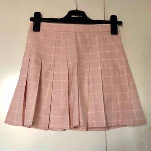Ljusrosa och vit rutig tenniskjol från koreanska märket Chuu. Har inbyggda shorts, så kjolen funkar att ha när det blåser! Dragkedja baktill. Säljer pga för liten💞 Frakt tillkommer! (Första bilden visar färgen bäst)