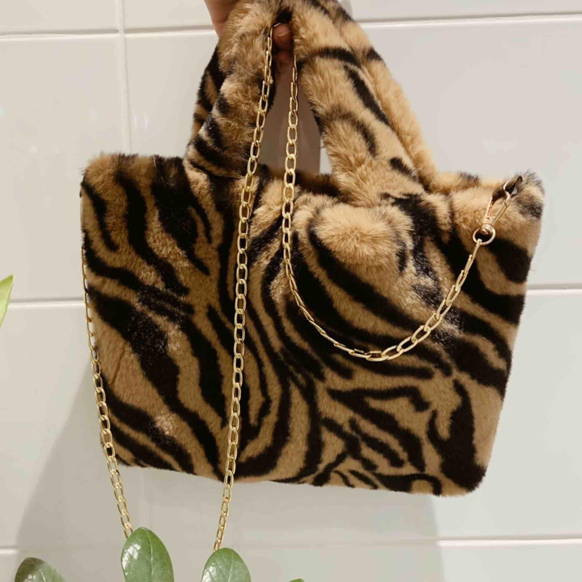 Fin väska i djurmönster, nyskick. 31x23cm. Smal guldkedja som axelrem. Frakt 44kr 💫. Väskor.