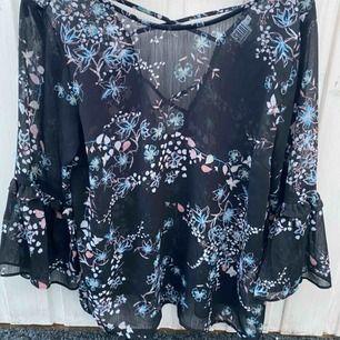 En fin blus med blommigt mönster, halvt öppen där bak med tunna band ifrån Saint Tropez Nypris: ca 500kr
