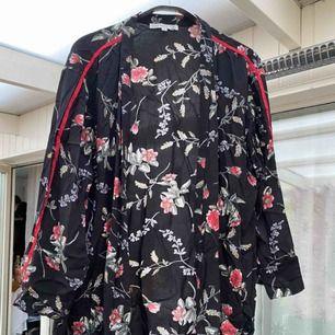 Säljer en tunn kimono, svart med blommigt mönster och en röd rand på längst armarna.  Märke: flash Nypris: ca 400kr Frakt ingår i priset!