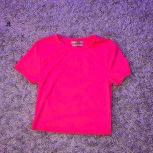 Neonrosa T-shirt från Pull & Bear. Säljer pga används inte. Kan skicka bild med tröjan på privat om du är intresserad. Frakt ingår ej i priset. Den har några hemmagjorda stygn på sidan längst ner, därav det billiga priset, annars är den som nyskick.