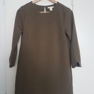 Mossgrön / mörkgrön klänning från h&m, strlk 34. Tjockt stadigt tyg! Har rundade kanter vid ärmslut och nedre kanten.