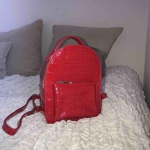 Röd lackryggsäck från Bershka Frakt ingår i priset