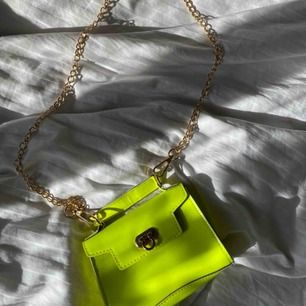 Liten väska i neon gul/grön med guld kedja! Köpt för ett tag sedan men är ej använd. Skriv till mig om du är sugen!