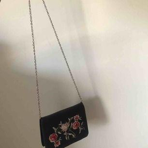 Svart väska med blommor på framsidan, tunn kedja som väskband