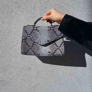Helt ny, aldrig använd väska från märket Beck Söndergaard. Väskan är i skinn och har ett tillhörande axelband. I mått 23x15cm.  Nypris 1399kr.