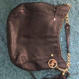 Nästintill oanvänd Michael Kors Väska i fint skick. Bra med fack och inredning, äkta svart läder.  Bred: 35 cm Högd: 30 cm