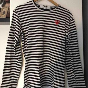 COMME DES GARÇONS PLAY tröja i storlek L. Ganska liten i storlek då den kryper ca en storlek vid första tvätten. Så mer som en M. Frakt ingår i priset.