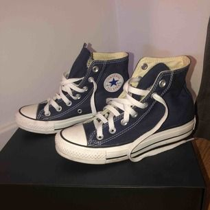 Ett par mörkblå höga Converse som endast är använda en gång. De är i storlek 35, men fungerar lika bra för en 36 (min erfarenhet).