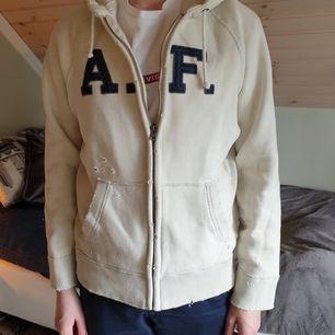 Abercrombie and fitch hoodie med dragkedja. Storlek S I herrstorlek. Slitningar på hoodie (de ska vara där). Knappt använd. Passar både tjejer och killar. Frakt tillkommer.