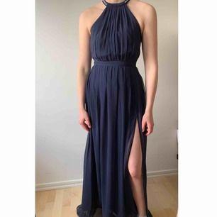 Fin mörkblå balklänning från Nelly med slits och fina pärldetaljer! Använd en gång. Storlek 34 men passar mig som är 171 cm. Köparen står för frakt!!