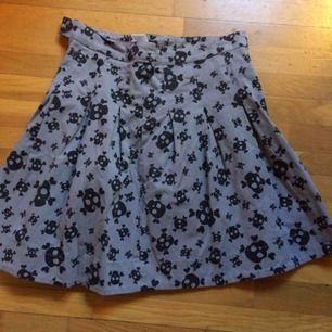 Sparsamt använd grå klockad kjol med svarta döskallar. Storlek 38. Priset är inkl vanlig frakt 🌸