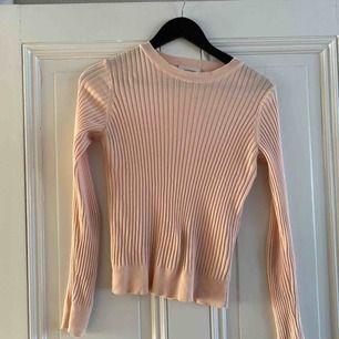 En rosa, lite peach färgad fin tröja från Monki. I perfekt skick!   I storlek xs men skulle säga att den passar större storlekar också.