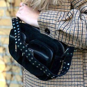Den populära Celina väskan i mellan från Noella. Väskan är i konst mocka och har nitar. Väskan har ett avtagbart långt band och ett kort band. Väskan är i gott skick och knappt använd.