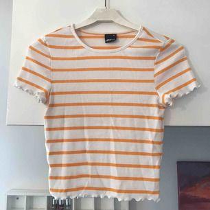 Söt topp från Gina Tricot i trendig modell: t shirt med små volanger vid ärmarna och nedtill. Vit och gulrandig. Storlek XS och i bra skick🌼✨💕