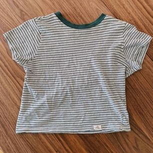 Tight croppad t-shirt med ljusgrå och gröna ränder. Använd några gånger, men i fint skick! Köpt på pull&bear för ca 2 år sen.