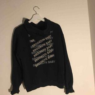 Svart hoodie från Na-KD med tryck på ryggen.