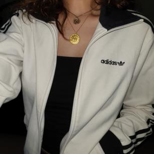 vit och svart adidas jacka i utmärkt skick! storleken är xs men är lite oversized och passar nog mer som en s. loggan är broderad