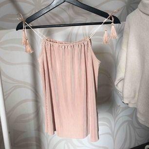 Ljusrosa linne i plisserat material med tofsar på axlarna från H&M, använd ett fåtal gånger 📦 frakt 60:-