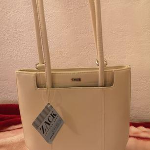 Jättefin vit axel/ryggväska från ZACK köpt i butik. Helt oanvänd med produktlapp kvar. Kan bäras på axel eller rygg. Vit läderimitation med stort innerfack samt två mindre fack med dragkedja.  Nypris 399. Pris 200 kr+ev frakt. Finns i Sthlm/Uppsala