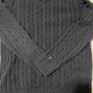 Marin blå Tommy Hilfiger stickat tröja i storlek S för män. Produkt i god form, gjord av 100% bomull, varm och passar bra under höst/vinter. Logo vid vänster hand. Tvättinstruktioner (maskintvätt)